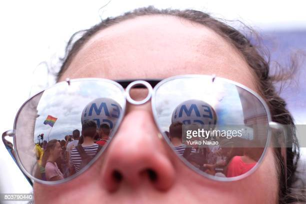 People attending a rally are reflected on a participant's sunglasses ahead of the Paris Gay Pride Parade or known as Marche des Fiertés LGBT in...
