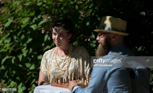 People attending Dardanella a Great Gatsby Lawn party play a game of chess near the National Cathedral in Washington DC on September 23 2017...