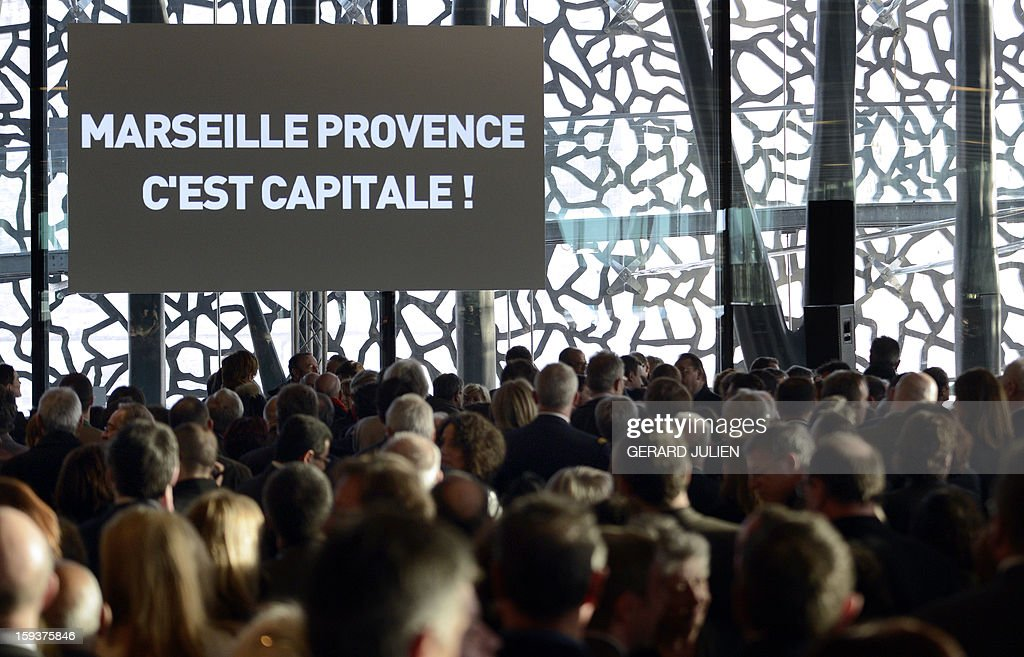 People attends a New Year wishes ceremony to French Culture, on January 12, 2013 in Marseille,in the southern French city of Marseille, in the Provence region, on the construction site of the Museum of Civilisations from Europe and the Mediterranean (MUCEM) designed by Italian architect Rudy Ricciotti, as part of the launching of Marseille-Provence 2013 European Capital of Culture. The event marks the start of a year, leading to a cultural renaissance in France's second-largest metropolitan area. AFP PHOTO / GERARD JULIEN