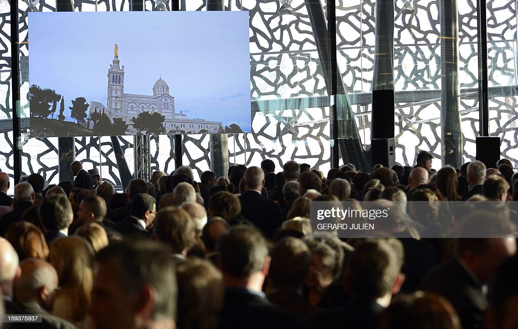 People attends a New Year wishes ceremony to French Culture, on January 12, 2013 in Marseille,in the southern French city of Marseille, on the construction site of the Museum of Civilisations from Europe and the Mediterranean (MUCEM) designed by Italian architect Rudy Ricciotti, as part of the launching of Marseille-Provence 2013 European Capital of Culture. The event marks the start of a year, leading to a cultural renaissance in France's second-largest metropolitan area. On the screen, Notre-Dame de la Garde basilica, emblem of the city which is topped by a statue of 'The Madonna and Child'. AFP PHOTO / GERARD JULIEN
