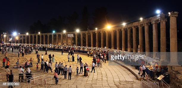 People attent the opening of the 30th Jarash Festival of Culture and Arts in the ancient Roman city of Jarash 50 kilometres north of the Jordanian...