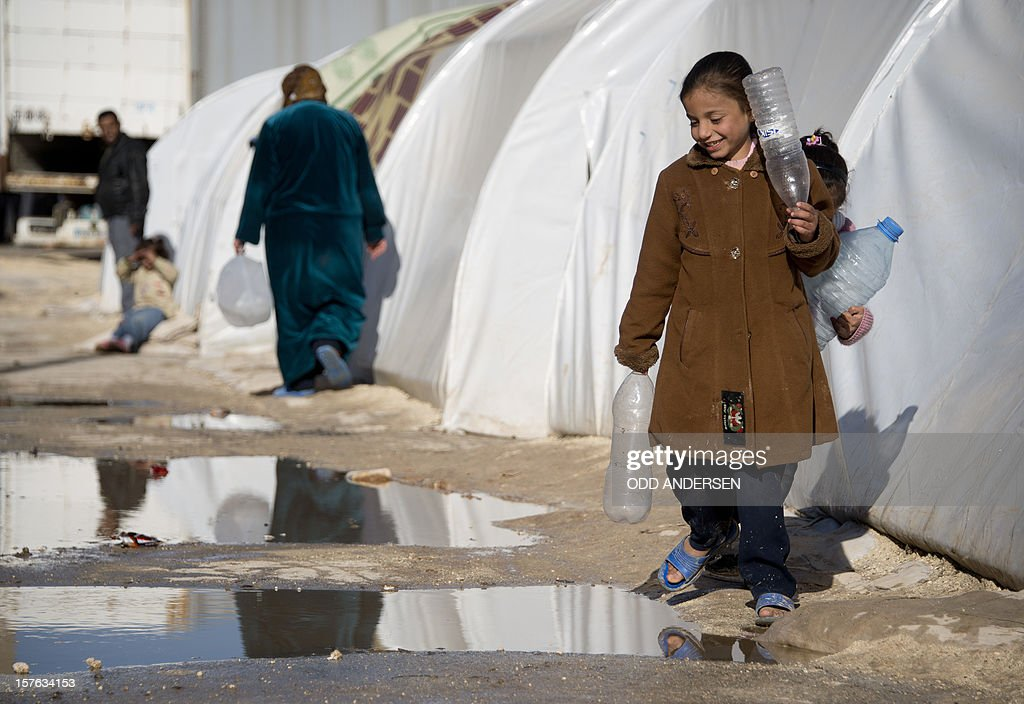 People avoid puddles of rainwater as they move along the rows of temporary accomodation in a refugee camp on the border between Syria and Turkey near the northern city of Azaz on December 5, 2012. The internally displaced faced further misery as heavy rain was followed by a drop in temperatures. The United Nations estimated late October that more than 2.5 million people have been affected by the fighting in Syria. There are more than 348,000 Syrian refugees registered in neighbouring countries, but many more are unregistered.