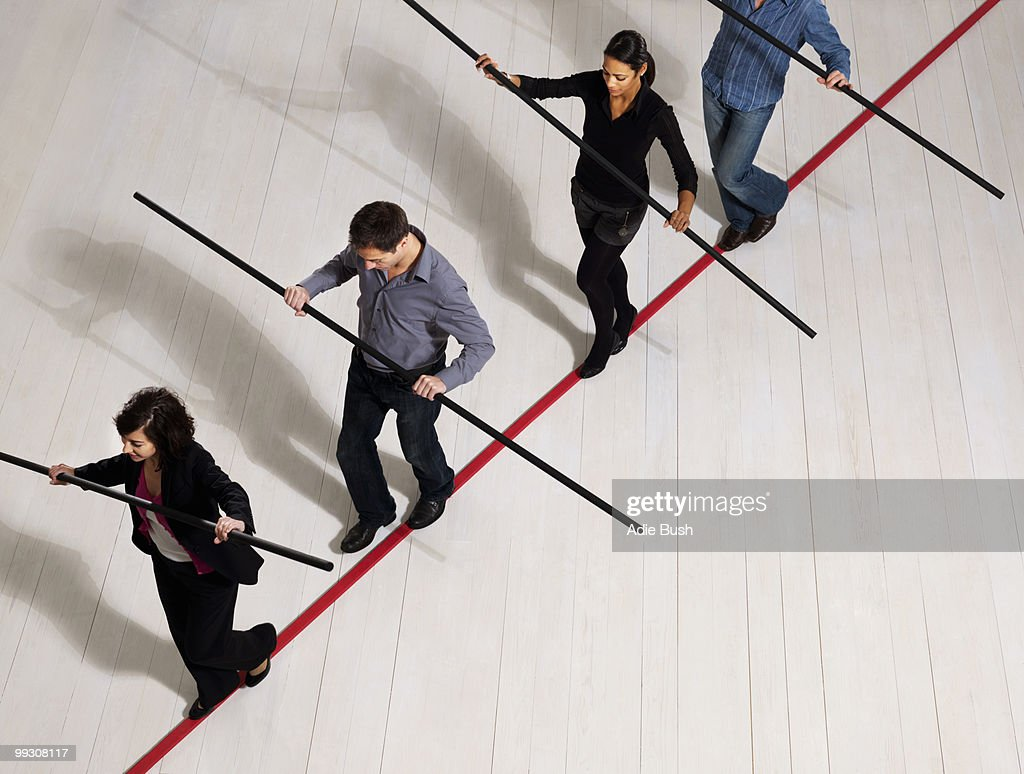 People balancing on thin red line : Stock Photo