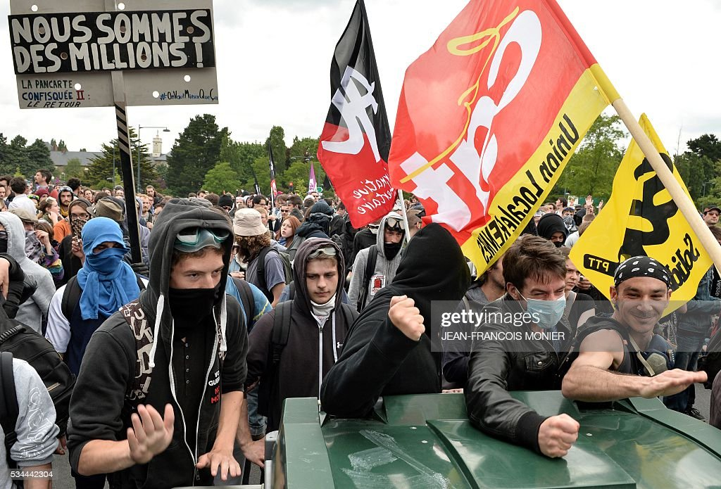People bang a plastic bin as they hold a placard reading ' we are millions' (L) and a flag of the French union-trade General Confederation of Labour (CGT) during a protest against the government's labour law reforms in Rennes, on May 26, 2016. The French government's labour market proposals, which are designed to make it easier for companies to hire and fire, have sparked a series of nationwide protests and strikes over the past three months. Masked youths clashed with police and striking workers blockaded refineries and nuclear power stations on May 26 as an escalating wave of industrial action against labour reforms rocked France. / AFP / JEAN