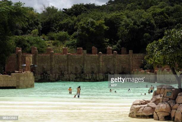 People bath in the artificial sandy beach of the Lost City water park in Sun City on February 22 2010 The shaking walkway leading to a manmade sandy...