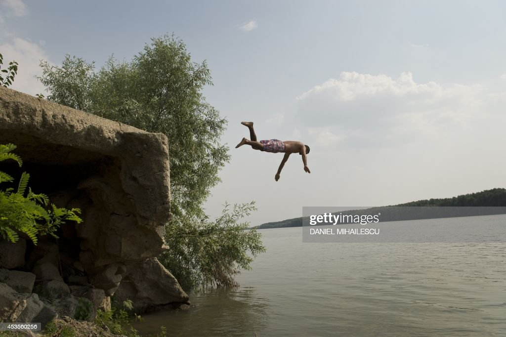 People bath on the banks of the River Danube in Peceneaga village (220 km east from Bucharest) August 13, 2014. Forecasters have issued an alert announcing temperatures of up to 38 degrees Celsius.