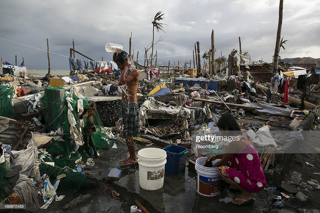 People bathe and wash clothes among the ruins of their neighborhood in Palo, the Philippines, on Monday, Nov. 18, 2013. Super Typhoon Haiyan slammed into the central Philippines on Nov. 8, knocking down most buildings, killing thousands, displacing 4 million people and affecting more than 10 million. Photographer: Paula Bronstein/Bloomberg via Getty Images
