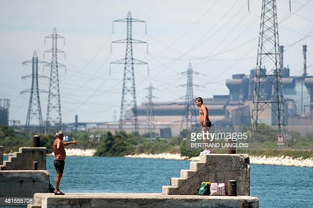 People bathe in the sea next to an industrial area in Fossur Mer southern France on July 22 while ozone pollution reached peaks in the BouchesduRhone...