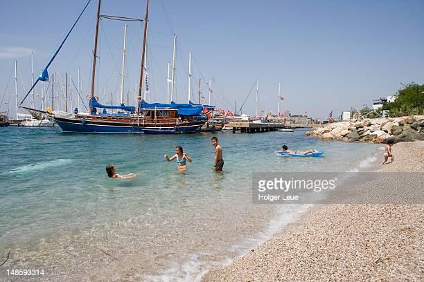 People bathing at beach with sailboats at marina.