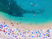 People bathing in the sun at the beach, aerial view with clear blue water and sandy beach. Corfu island Kerkyra, Greece, Europe.