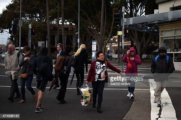 People battle with the strong wind as they cross the main road near Manly Warf in Sydney on May 22 2015 Earlier a severe weather warning was issued...