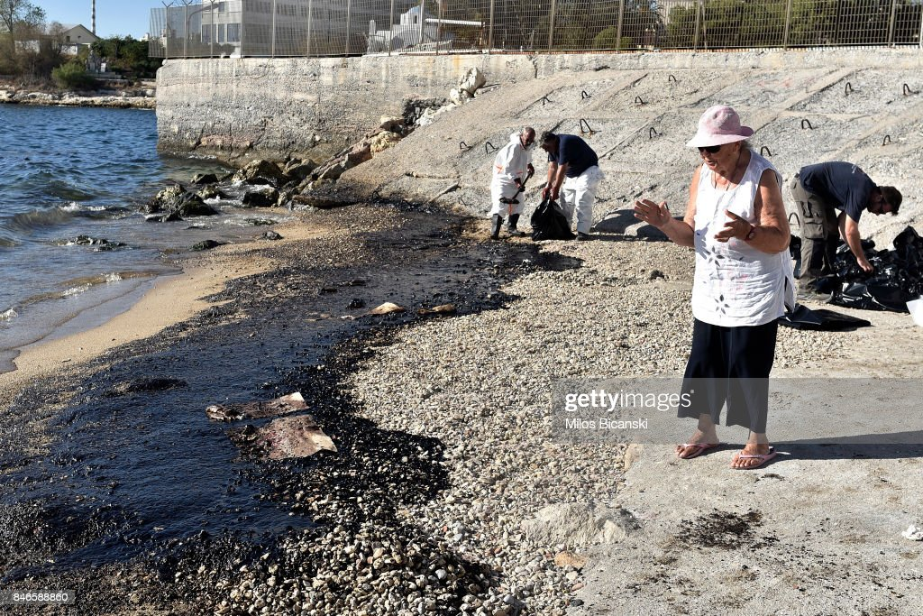 People begin to clear oil from a polluted beach on the coast of Salamis Island on September 13, 2017 in Salamis, Greece. The small tanker 'Agia Zoni II' sank on September 10, whilst anchored off the coast of Salamis, near Greece's main port of Piraeus. It was carrying a cargo of 2,200 tons of fuel oil and 370 tons of marine gas oil. Salamis Island has suffered heavy pollution as a result in what has been called a 'major environmental disaster' by officials.