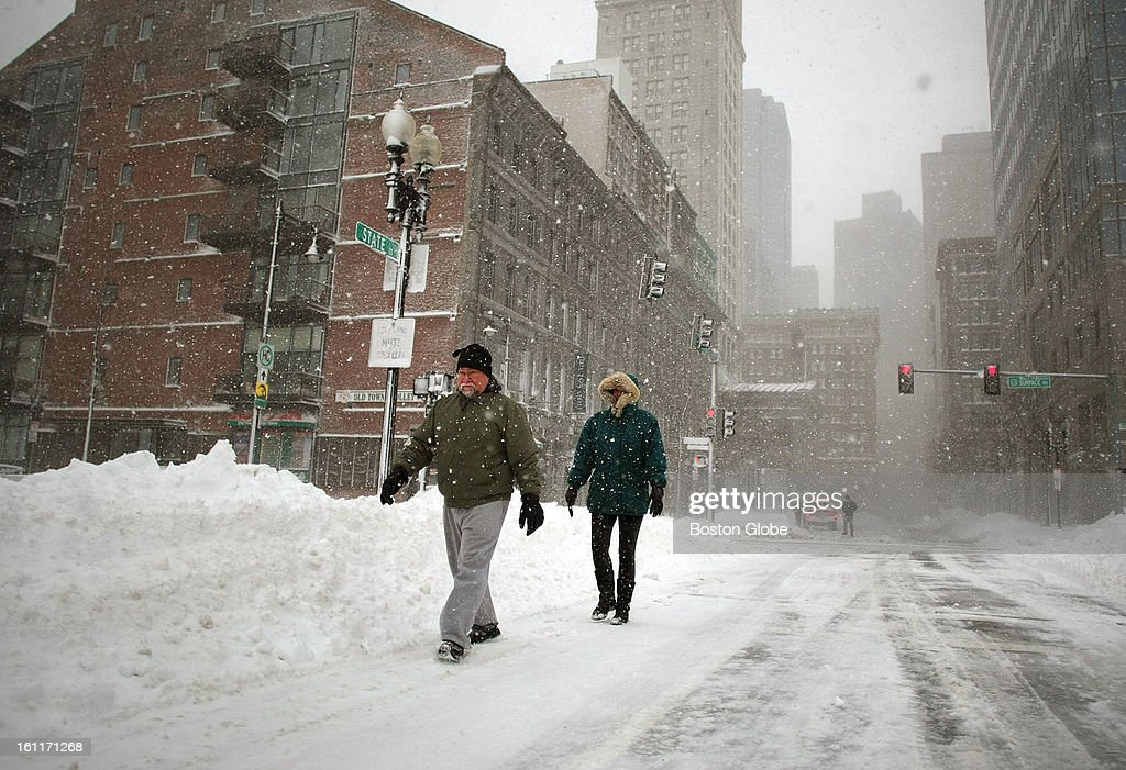People begin to dig out from the big blizzard. A couple walk along State Street towards the waterfront.