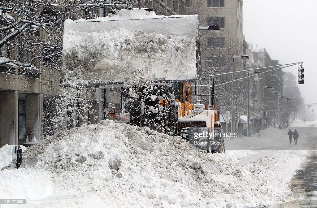 People begin to dig out from the big blizzard. A front end loader clears snow on Massachusetts Avenue.