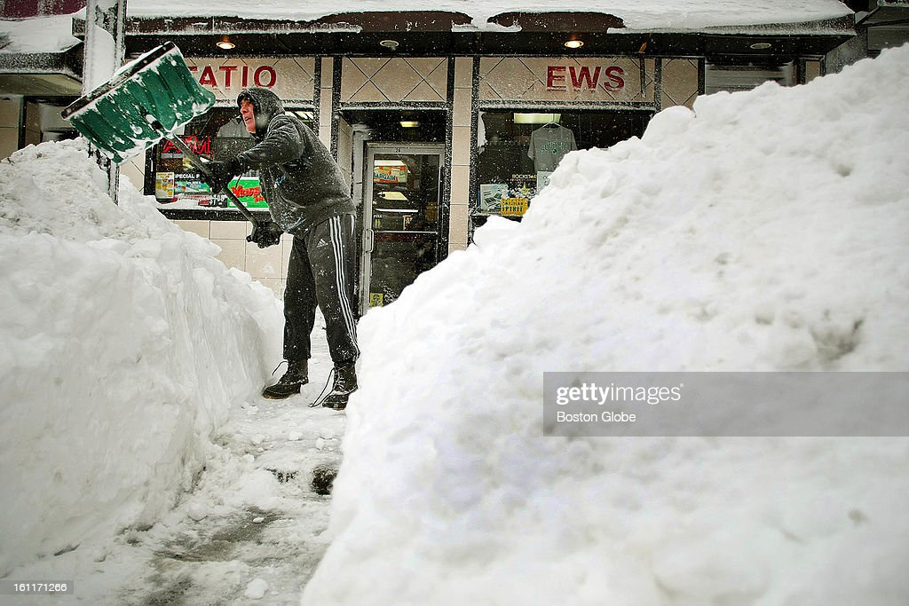 People begin to dig out from the big blizzard. Mike Lewis clears a path to his store on West Broadway in South Boston.