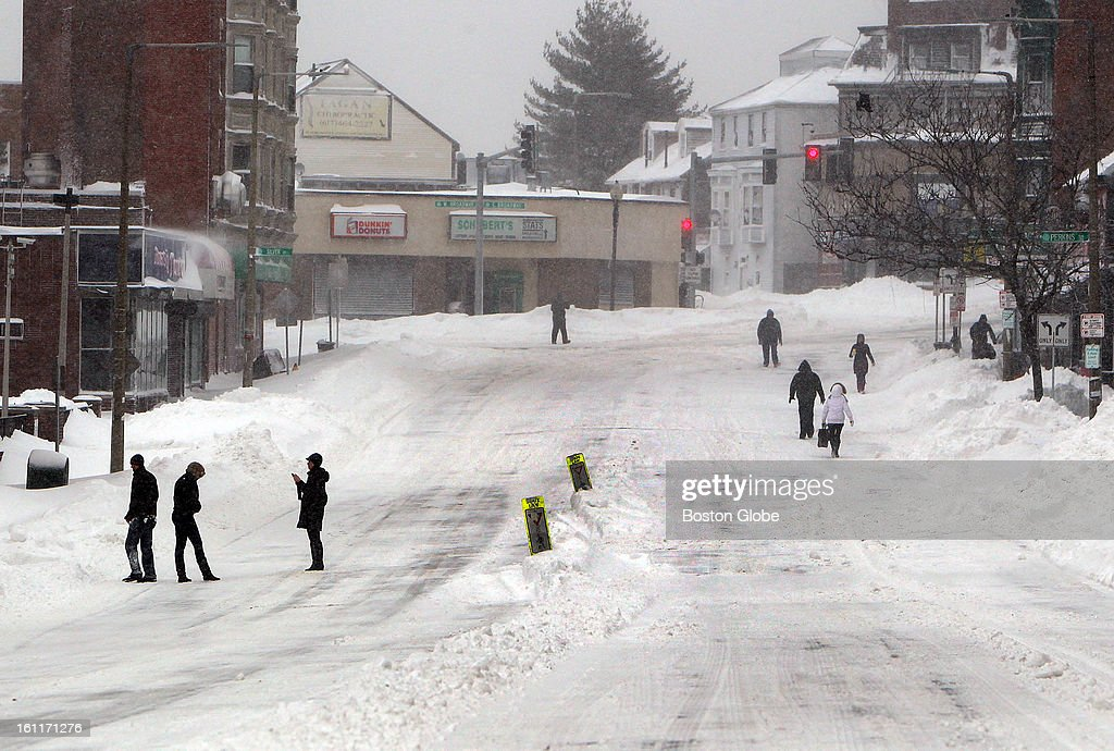 People begin to dig out from the big blizzard. People walk along Dorchester Street in South Boston.