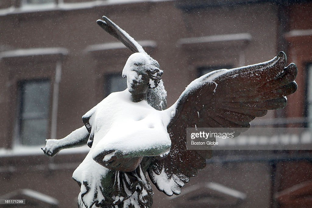 People begin to dig out from the big blizzard. The angel statue in the Boston Public Garden is covered with snow.