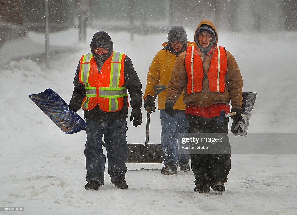 People begin to dig out from the big blizzard. Workers carry shovels on State Street in the financial district.