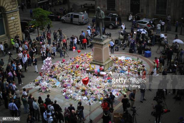 People begin to gather around floral tributes to the victims of the Manchester attack ahead of ahead of a vigil by religous leaders from across...