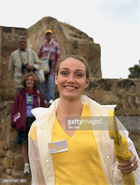People behind woman wearing name tag, portrait (focus on woman)