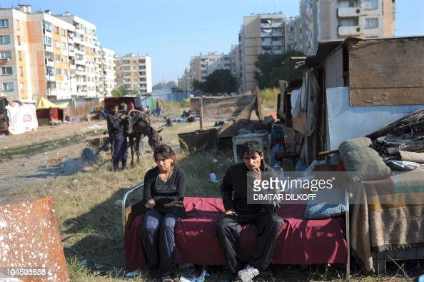 People belonging to the Roma community sit near their shack in a makeshift camp as the huge holedout shell of an apartment building and the pungent...