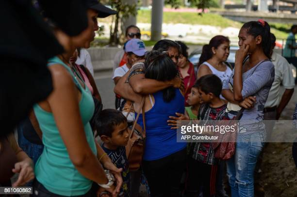 People bid farewell to relatives before boarding a bus at a station in Caracas on October 11 2017 as scores of disappointed Venezuelans who see no...