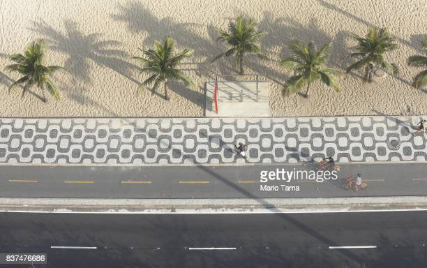 People bike along Ipanema beach during the traditionally low tourist season on August 14 2017 in Rio de Janeiro Brazil Rio de Janeiro's hotels have...