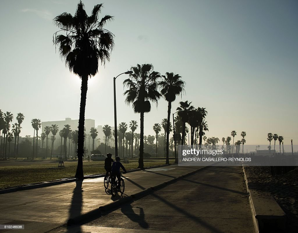 People bike along the beach in Santa Monica, California on February 14, 2016. / AFP / ANDREW CABALLERO-REYNOLDS