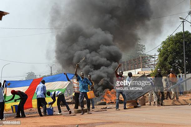 People block a road as they protest against the French 'Sangaris' intervention in the Galabadia neighborhood close to the Centrafrican President's...