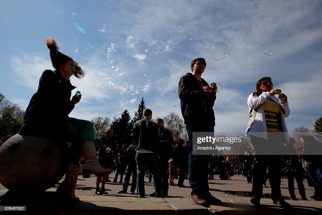 People blow soap bubbles during the Dreamflash soap bubble festival at the Pervomaisky Square in Novosibirsk, Russia, on April 30, 2016.