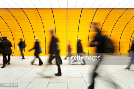 People blurry in motion in yellow tunnel down hallway