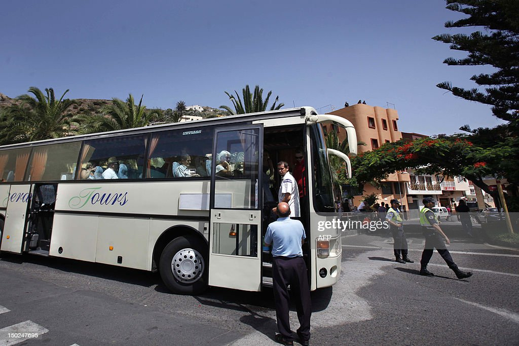 People boar a bus during an evacuation in Vallehermoso, on August 13, 2012, on the Spanish canary island of La Gomera. Wildfires killed two people in southeastern Spain and forced thousands to evacuate in the Canary Islands where flames ravaged a rare nature reserve, authorities said Monday.