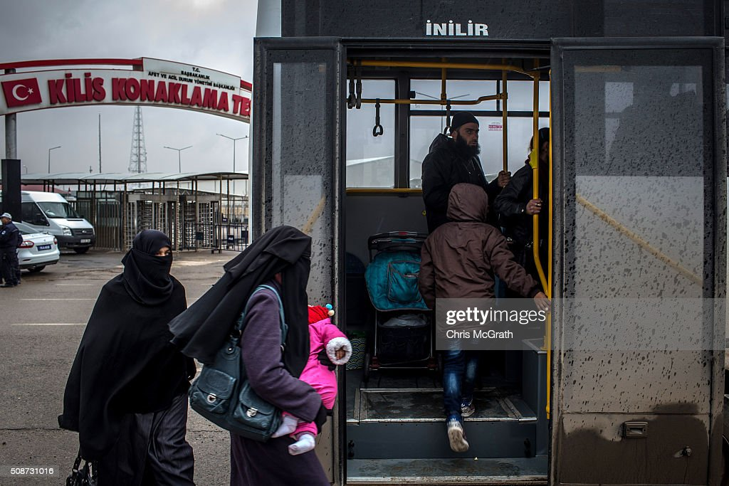 People board a bus to Kilis town center from the closed Turkish border gate on February 6, 2016 in Kilis, Turkey. According to Turkish officials some 35,000 Syrian refugees have massed on the Syrian/Turkish border after fleeing Russian airstrikes and a regime offensive surrounding the city of Aleppo in northern Syria.