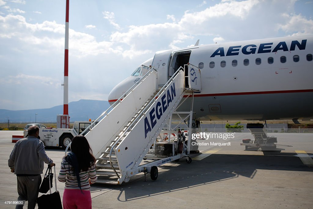 People board a parked airbus A320 from the flight company Aegean at the Santorini Airport field on June 10 2015 in Santorini Greece Santorini is an...