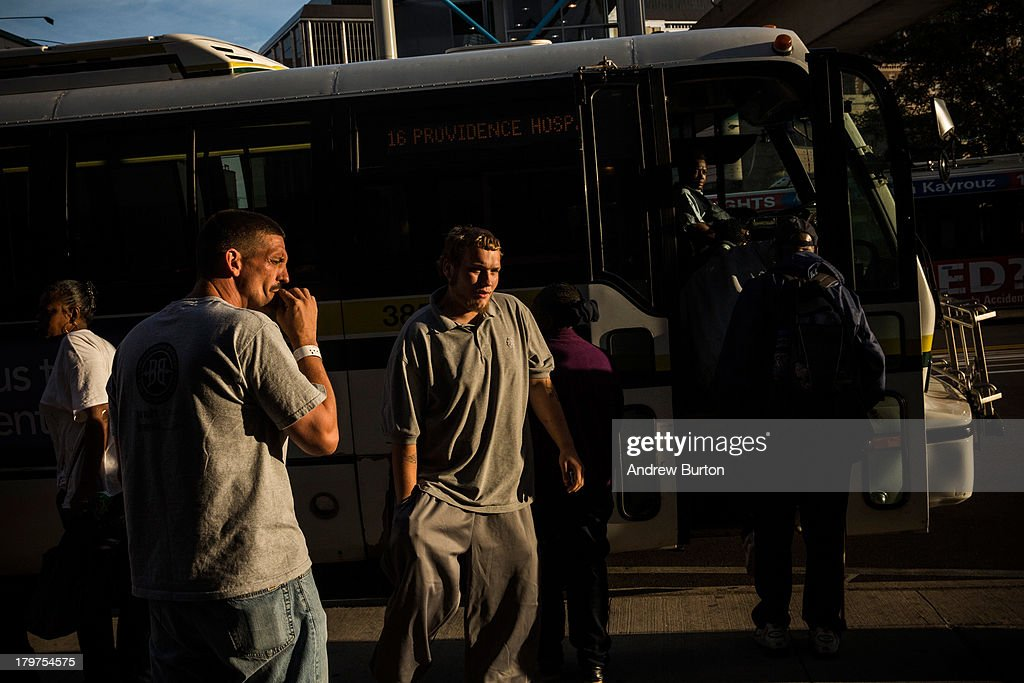 People board a public transit bus on September 6, 2013 in Detroit, Michigan. Detroit is struggling with over 78,000 abandoned homes across 140 square miles and 16% unemployment; in July, the city declared bankruptcy.