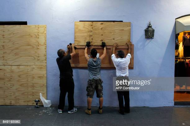 TOPSHOT People board up windows of a business in preparation for the anticipated arrival of Hurricane Maria in San Juan Puerto Rico on September 18...