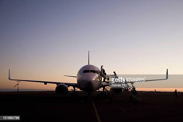 People boarding an airplane at dusk,  Port Hedland, Western Australia, Australia