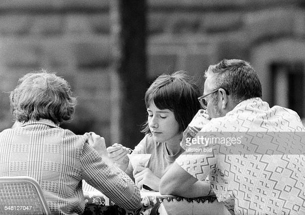 people bored young girl and her parents sit in a beer garden nibbling ice cream father drinks a beer girl aged 14 to 16 years father aged 40 to 50...