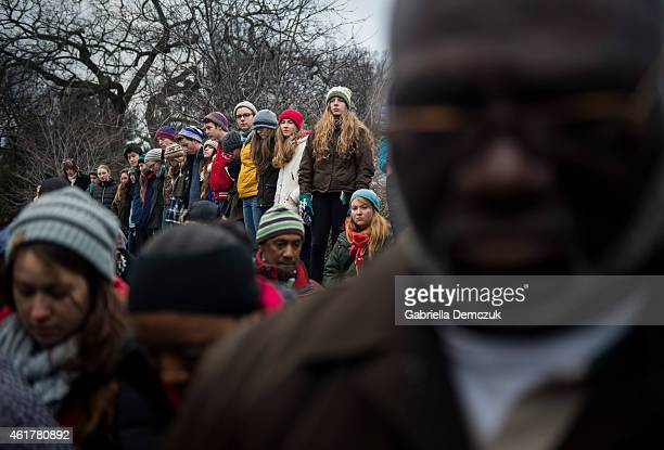 People bow their heads during a wreath laying ceremony at the Martin Luther King Jr Memorial on the National Mall on MLK Day January 19 2015 in...
