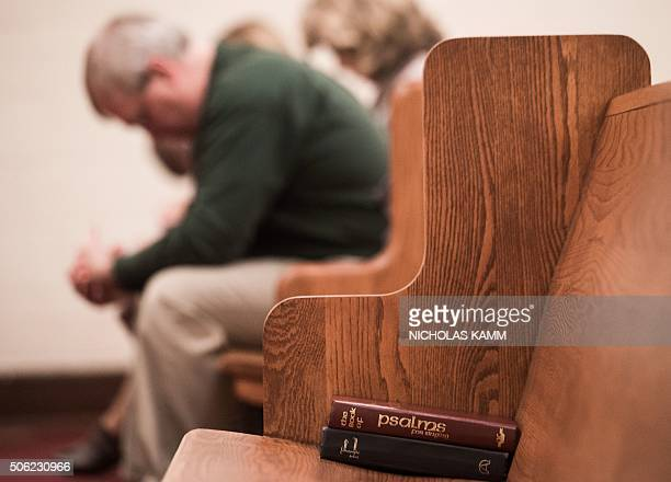 People bow their heads in prayer during a Sunday evening service at Grace Orthodox Presbyterian Church in Lynchburg Virginia on January 17 2016 The...