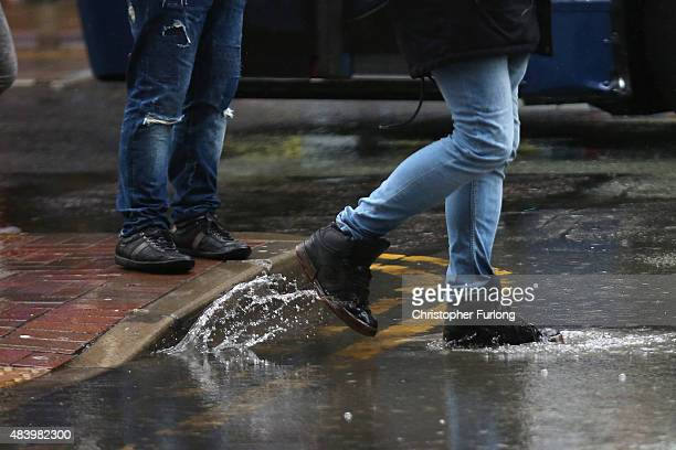 People brave a downpour in Manchester City centre on August 14 2015 in Manchester England Heavy rain and flood warnings have been issued by the Met...