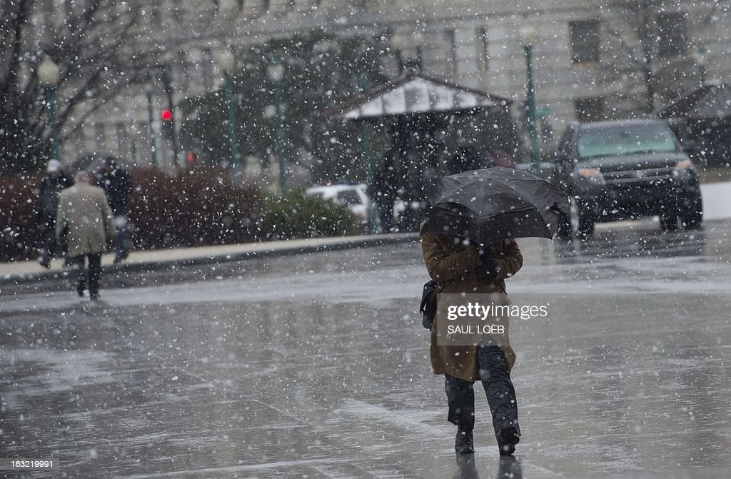 People brave cold high winds and snow at the US Capitol in Washington, DC, March 6, 2013 during a storm. Federal offices and many schools have closed in preparation for a mix of snow, sleet and rain which could account for the area's largest winter storm in two years.AFP PHOTO / Saul LOEB