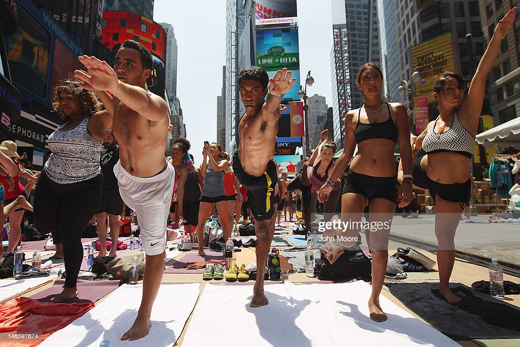 People brave high temperatures while practicing bikram yoga as part of the annual Mind Over Madness event in Times Square on June 20, 2012 in New York City. The event is held annually on the summer solstice, the longest day of the year and the first day of summer, amidst the hussle and bustle of Times Square, considered one of the busiest places on earth.