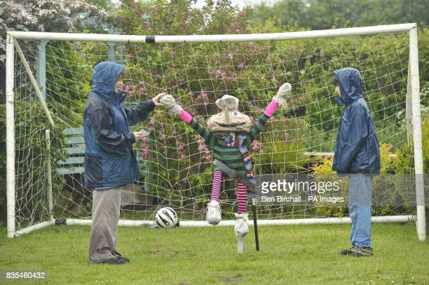 People brave the rain to take part in a scarecrow trail in the village of Norton St Philip Somerset and tick off scarecrow number 12 Spud as all the...