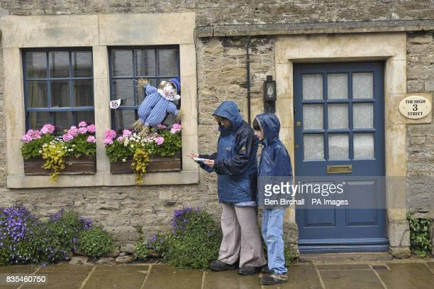 People brave the rain to take part in a scarecrow trail in the village of Norton St Philip Somerset and tick off scarecrow number 16 Andy Pandy as...