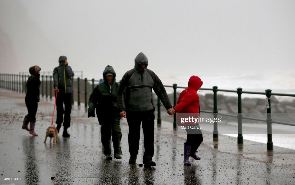 People brave the stormy weather and walk besides the beach on December 23, 2013 in Sidmouth, England. The Met Office has issued a number of severe weather warnings for heavy rain and high winds and is warning that it may lead to some travel disruption as people travel for Christmas.