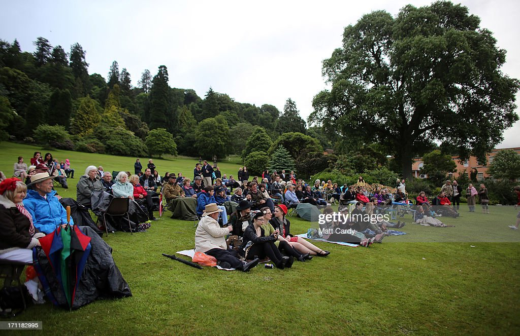 People brave the wind and rain to watch the evening entertainment in the gardens at Killerton House on June 22, 2013 in Exeter, England. The National Trust property, near Exeter, is holding a two day vintage weekend with stalls selling vintage fashion, home ware and crafts, displays of classic cars and features an evening of entertainment which includes burlesque dancers.