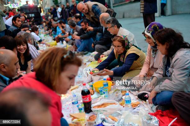 People break their fast as police patrol with a water cannon on May 27 2017 near Taksim Square in Istanbul during the first day of the holy month of...