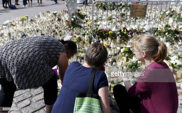 People bring candles and flowers to the makeshift memorial for the victims of the stabbings at the Turku Market Square Finland on August 20 2017 Two...
