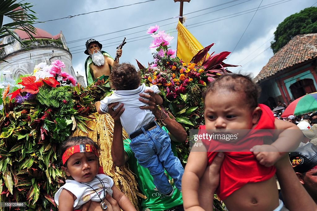 People bring children closer to the image of San Jeronimo, the patron saint of Masaya, during celebrations in his honour, in Masaya, 30 km from Managua, on September 30, 2012. During the procession the image of San Jeronimo is taken from the San Jeronimo church to Nuestra Señora de la Asuncion church and back. AFP PHOTO/Hector RETAMAL